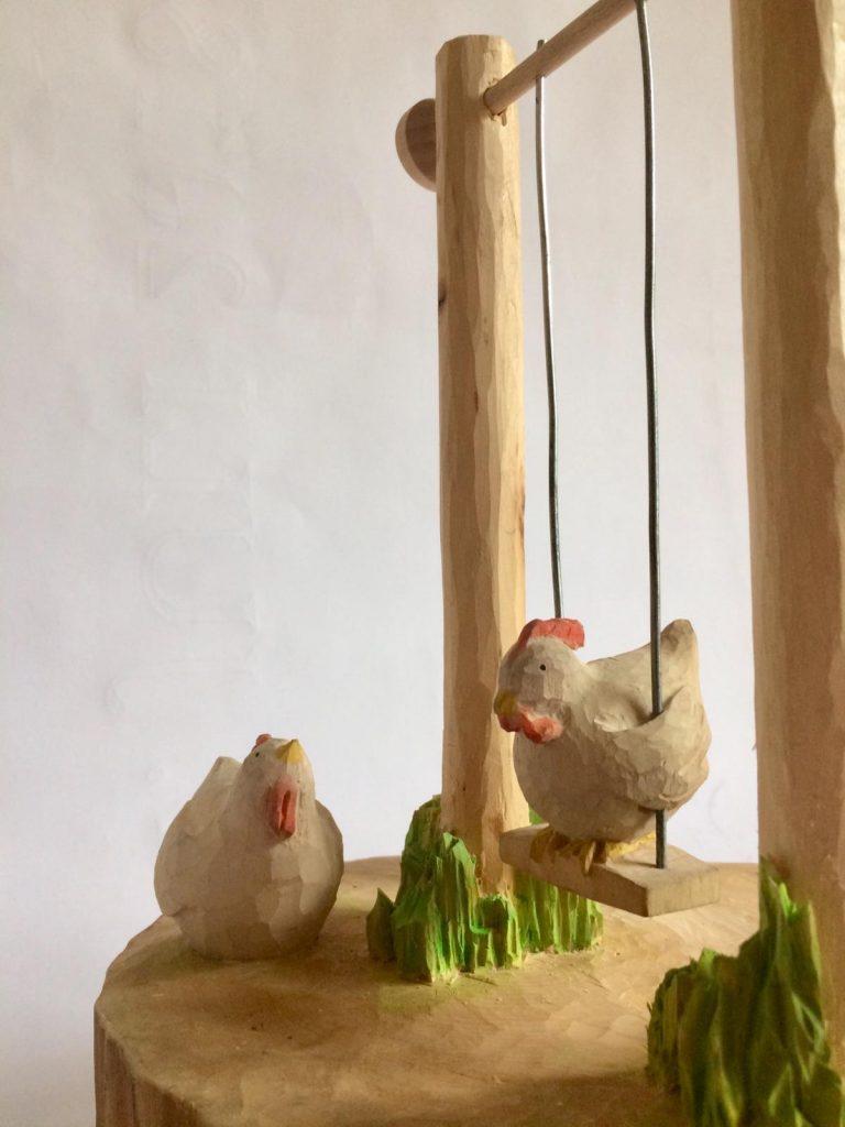 Ein Huhn auf einer Schaukel aus Linde geschnitzt, beweglich